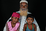 Pictured: Tasnim, Medhi and their grandfather Shukur Mia <br /> <br /> Family members with an unusual pigmentation show off their shockingly bright, blue eyes.  Eyes of this colour are rare for people of a darker skin tone, and the cause is a lack of melanin pigment in the iris of the eye.<br /> <br /> Lower levels of melanin are more commonly found in people with lighter skin tones, meaning they are more likely to have lighter coloured eyes.  The grandfather's name is Shukur Mia, who is photographed with his granddaughter Tasnim, 11, and grandson Mehedi, 6.  SEE OUR COPY FOR DETAILS.<br /> <br /> Please byline: Sultan Ahmed Niloy/Solent News<br /> <br /> © Sultan Ahmed Niloy/Solent News & Photo Agency<br /> UK +44 (0) 2380 458800