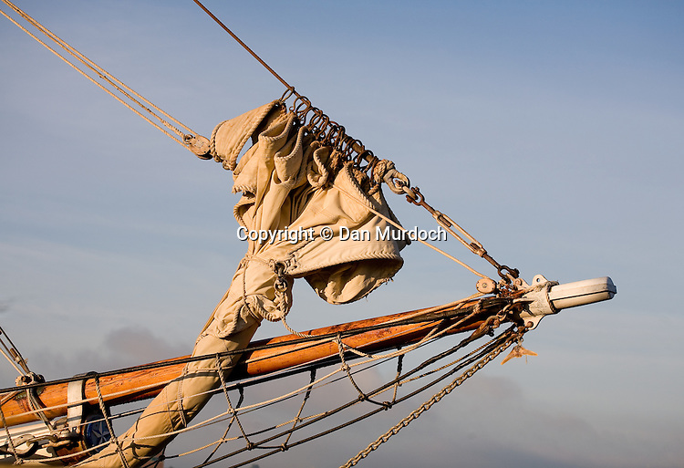 Furled sail and bowsprit of classic schooner in morning sun