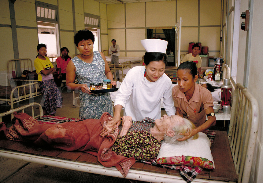 Inside the womens' ward of the only hospital in Yangon, Myanmar for infectious diseases, a nurse offers compassion to an elderly, woman patient. medical care, occupations, trades, Burma. Womens' ward in hospital. Yangon, Myanmar Hospital in city.