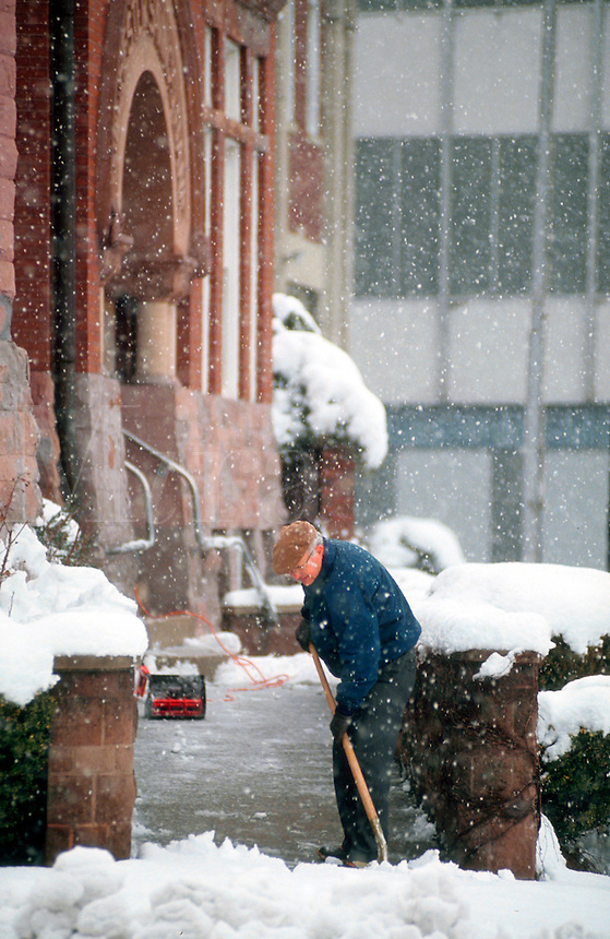 Man shoveling snow from walkway in front of public building.
