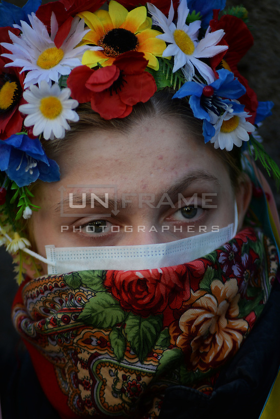 A peaceful demonstrator wears flowers costume  in Maidan square. Kiev, Ukraine
