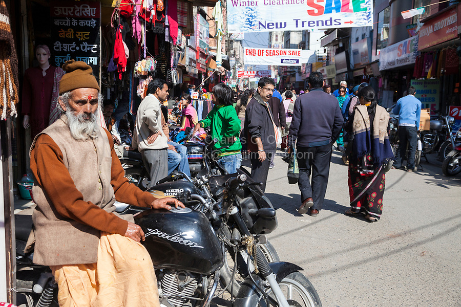 India, Dehradun.  Street Scene on a Busy Market Street.  The man sitting on the motor bike has a bindi between his eyebrows, representing the third eye or spiritual sight that Hindus seek.  It is also said to protect against demons or bad luck.