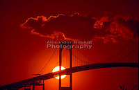 Sunset behind pilings of Newport Bridge in Newport Ri.