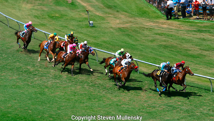 Jockeys crowd the rail in the first turn on the turf course at the Del Mar Thoroughbred Club in Del Mar, California.