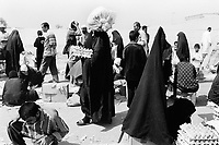 """Iraq. Baghdad. Al Sadr City. The women wear the """"abaya"""" (body-covering black garments) and the """"hidjab"""" (islamic headscarf) on their heads to cover the hair. Women shop in the open air market . © 2003 Didier Ruef"""