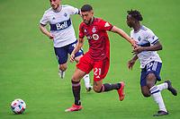 ORLANDO, FL - APRIL 24: Jonathan Osorio #21 of Toronto FC dribbles the ball during a game between Vancouver Whitecaps and Toronto FC at Exploria Stadium on April 24, 2021 in Orlando, Florida.