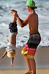 Jacob Koch (right) finds holding his nephew Ethan Armoire (age 4) (both live in Hawaii) by his legs, he can get a under-side-down view of the surfing at Ehukai Beach (Banzai Pipeline) on the Northshore of Oahu, Hawaii over the President Day Weekend.