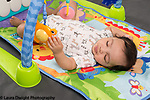 4 month old baby boy on back under hanging toy bar, holding toy with palm