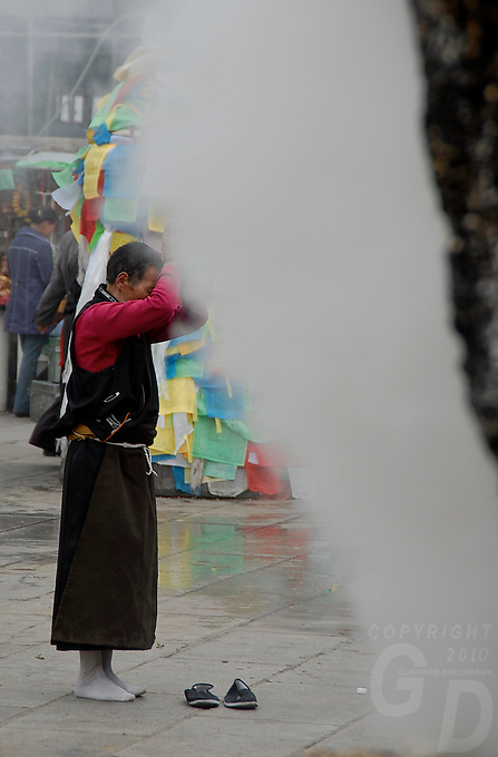 The central part of Barkhor street is coverd in smoke, pilgrims burning their incense in giant Burners right in front of Jokhang Temple,Lhasa.The Jokhang Temple is one of Tibet's holiest shrines, originally built in 647 A.D. in celebration of the marriage of the Tang Princess Wencheng and the Tubo King Songtsen Gampo. In front of the gate is a stone Tablet of Unity from the Tang Dynasty; inscribed are both Chinese characters and Tibetan script. Nearby is the stump of the willow tree said to have been planted by Princess Wencheng herself; two younger willow trees now flank the stump of the first tree...Located in the center of old Lhasa, the temple was built by craftsmen from Tibet, China, and Nepal and thus features different architectural styles. The temple is also the spiritual center of Tibet and the holiest destination for all Tibetan Buddhist pilgrims. In the central hall is the Jokhang's oldest and most precious object--a gold statue of a seated 12-year-old Sakyamuni. This is said to have been transported to Tibet by Princess Wencheng from her home in Changan in 700 A.D. Other precious antiques in the temple include a silk portrait of Buddha from the Tang Dynasty and a pearl gown and gold lamp from the Ming Dynasty. The three-leafed roof of the Jokhang offers splendid views of the bustling Barkhor market and across to the Potala Palace..