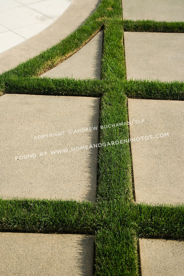 Close up detail of 4 inch wide strips of green grass defining the geometric pattern of concrete stepping stones.