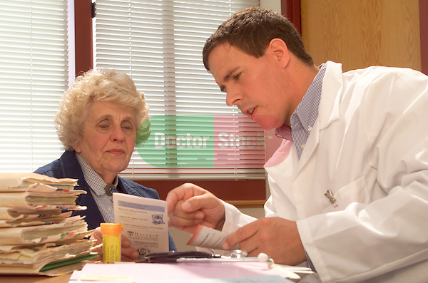 young male doctor consulting with older, elder female patient, reviewing prescription information, both sitting at desk in doctor's office