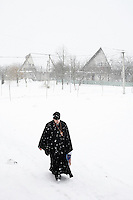 Father Momotyuk Nazarii, village priest at the church in Novo Ladizhichi, Ukraine, goes caroling to celebrate Ukrainian Orthodox Christmas. The choir spent two days going door to door all over Sukachi and Novo Ladizhichi villages, singing, offering blessings, and collecting donations for the church.  <br /> ------------------- <br /> This photograph is part of Michael Forster Rothbart's After Chernobyl documentary photography project.<br /> © Michael Forster Rothbart 2007-2010.<br /> www.afterchernobyl.com<br /> www.mfrphoto.com <br /> 607-267-4893 o 607-432-5984<br /> 5 Draper St, Oneonta, NY 13820<br /> 86 Three Mile Pond Rd, Vassalboro, ME 04989<br /> info@mfrphoto.com<br /> Photo by: Michael Forster Rothbart<br /> Date:  1/2009   File#:  Canon 5D digital camera frame 50497 <br /> ------------------- <br /> Original caption: .Father Momotyuk Nazarii, the village priest at the church in Novo Ladizhichi, Ukraine, goes Christmas caroling with members of his congregation to celebrate Ukrainian Orthodox Christmas, January 7, 2009. The group spent two days going door to door all over Sukachi and Novo Ladizhichi, singing, offering blessings, and collecting donations for the church. When people gave them candy and fruit, they redistributed it to children and elderly residents. Novo Ladizhichi was built in 1987 to house evacuees from the original village of Ladizhichi following the 1986 Chernobyl accident..
