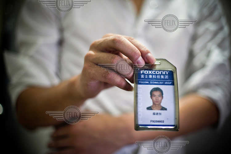 21 year old Yang Shu Heng shows his Foxconn factory pass. As well as access to the factory, the pass is credited with 160 RMB (16 GBP) monthly for purchases at the factory's convenience store. Foxconn is a Taiwanese technology company that makes products for Apple and Sony among others and is the largest private sector employer in China.