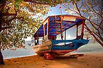 "A dive boat was originally pulled up onto the beach for repair.  Propped upright on the sandy beach near the entrance of the Siladen Resort and Spa, it has become an emblem and landmark for the resort, with the colorful sign ""Diving is Fun at Siladen Resort and Spa.""  (HDR image, on Siladen Island, Bunaken National Park, North Sulawesi, Indonesia.)"