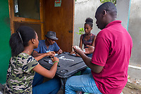 Haiti, Gros-Morne. Scholar girls through Mercy Beyond Borders doing community service at old people's home. Girls playing dominoes with the men.