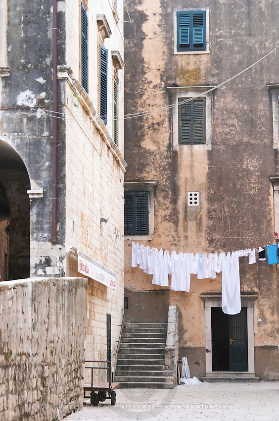 A small street with old houses and a clothes line with newly washed clothes hanging to dry in a back street Dubrovnik, old city. Dalmatian Coast, Croatia, Europe.