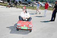 A Bektash Shriner drives a tiny car at the start of the Labor Day parade in Milford, New Hampshire. Republican candidates John Kasich, Carly Fiorina, and Lindsey Graham, and Democratic candidate Bernie Sanders marched in the parade.