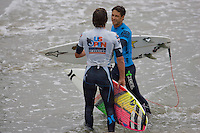 American Brett Simpson is congratulated by Nate Curran during the final day of the 2010 US Open of Surfing in Huntington Beach, California on August 8, 2010.
