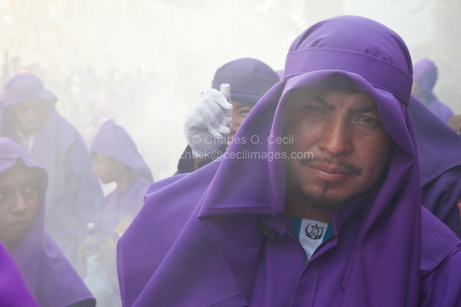 Antigua, Guatemala.   A Cucurucho Accompanying a Religious Procession during Holy Week, La Semana Santa.  Clouds of Incense Obscure others in Background.