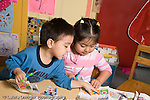 Educaton preschool  3-4 year olds fine motor literacy activity boy and girl cutting up catalogs and magazines talking and interacting  horizontal