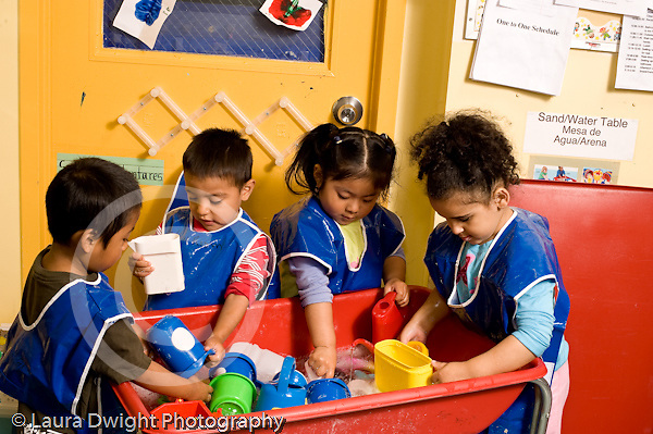 Education Preschool 3-4 year olds group of two boys and two girls playing at water table interacting horizontal