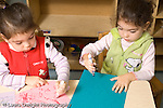 preschool 2-3 year olds identical twin girls in same class at school art activity using opposite hands to draw