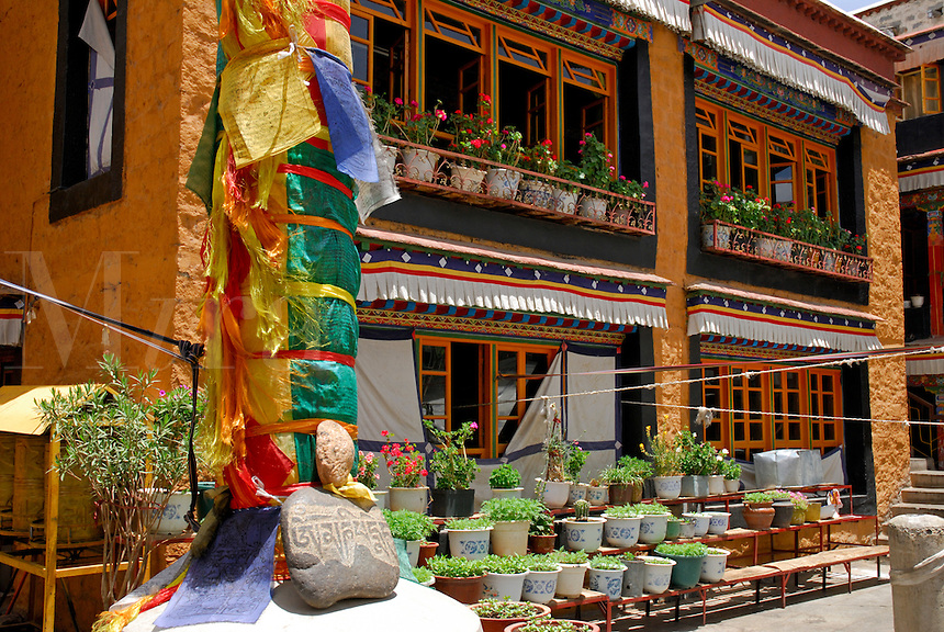 Courtyard of Ani Sanghkhung Nunnery with darchen, or prayer flag pole, mani, or prayer, stone carved with mantra Om Mani Padme Hum, and painted windows of prayer rooms, Lhasa, Tibet, China.