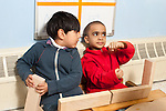 Education preschool 3-4 year olds two boys playing together in boat made of blocks one boy using a block tiller and the other steering