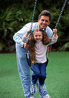 A smiling father and young daughter playing on a swing.