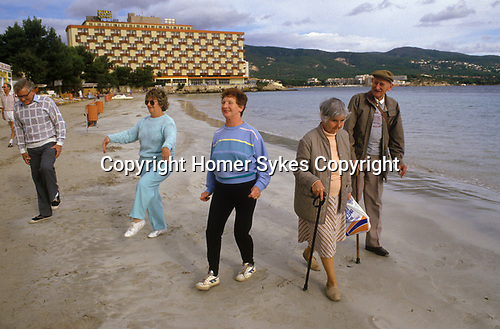 Young at Heart. British seniors on winter holiday in Balearic Islands Palma Nova Majorca Spain. Daily fun exercise class on beach led by the holiday rep. 1980s
