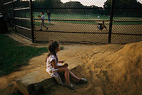 A young girls watches boys play ball in Propspect Park, Frederick Law Olmsted's favorite park that he designed, although Olmsted wouldn't approve of playing ball in his masterpiece.