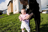 An Hasidic father plays with his child on the lawn in front of their rented house. Hasidic families stay in Pentre Jane Morgan university accommodation when they holiday in Aberystwyth. Every other day, bread, milk and other supplies are brought from Kosher shops in London and resold from one of the rented houses on the campus.