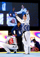 05 MAY 2012 - MANCHESTER, GBR - Aaron Cook (GBR) of Great Britain (on right, in blue) attempts to generate applause for his opponent after beating Ramin Azizov of Azerbaijan (crouched on left in red) to win the men's -80kg final in the 2012 European Taekwondo Championships at Sportcity in Manchester, Great Britain when the referee penalised Azizov for stepping out of the field of play in the final second of the last round to give Cook the title .(PHOTO (C) 2012 NIGEL FARROW)