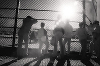 Watching ball game through chain link fence<br />
