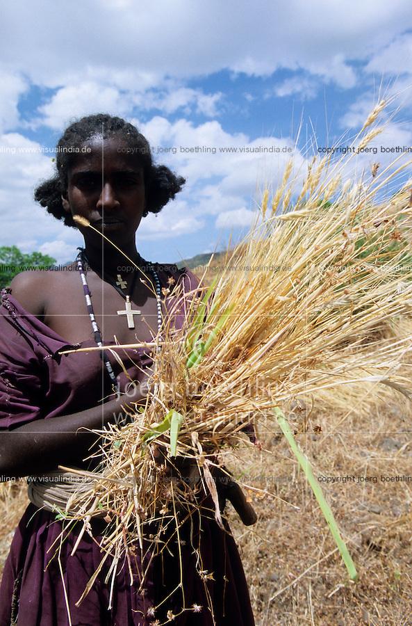 ETHIOPIA, Amhara, Lalibela , orthodox christian woman with cross necklace harvest wheat in highland / AETHIOPIEN, Lalibela, orthodox christliche Frau auf Feld bei Weizenernte im Hochland von Amhara