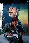 Marsh Arabs. Southern Iraq.  Marsh Arab young soldier, Basra - soldier smoking, in front of poster of Saddam Hussein in military uniform 1984