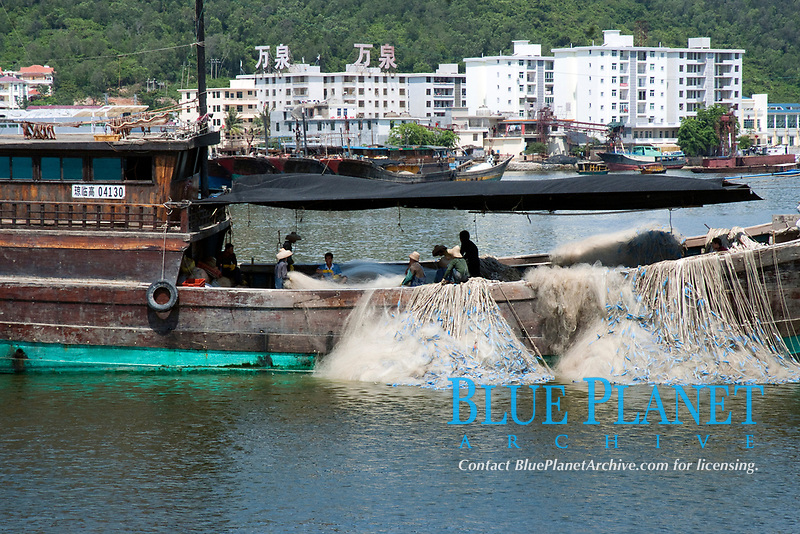Fishing boat moored in Sanya harbor whilst its nets are being mended, Hainan, China, South China Sea, Pacific Ocean