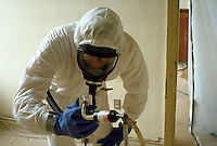 A worker monitors air quality during asbestos removal from an old school building. Health Hazards, Environment, Pollution, Masks, Protective Gear.