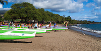 Islanders move outrigger canoes to the surf at Hanakao'o Beach Park, or Canoe Beach, Maui.