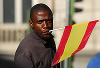 12/10/2007. Hispanidad Day. Colon square. Madrid. Spain. Flag Use Debate during the Arms Forces Parade. A black man wear a spanish flag in his mouth. The foreingpeople wear a lot of spainish flags show to the spanish people their integration in spain. Photo: Eduardo Dieguez/ DyD fotografos