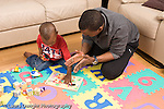 2 year old toddler boy with father interaction language development interacting with counting number puzzle and toys  praise clapping when puzzle finished horizontal African American