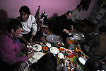 BASHMAKH, IRAQ: Tariq, the owner of a smugglers' den, eats dinner with smugglers...Iranian Kurdish smugglers traffic petrol from Iran into Iraq and alcohol from Iraq into Iran.  On foot, a smuggler can look to make around $10 per trip whereas with a horse a smuggler can make $100.  The routes are very dangerous with the risk of stepping on land mines or  being shot by the Iranian military..Photo by Kamaran Najm/Metrography