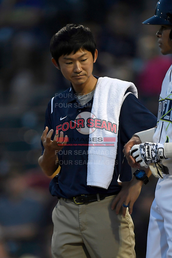 Trainer Hiroto Kawamura examines an injury in a game against the Augusta GreenJackets on Opening Day, Thursday, April 5, 2018, at Spirit Communications Park in Columbia, South Carolina. Columbia won, 4-2. (Tom Priddy/Four Seam Images)