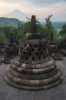 Borobudur, Java, Indonesia.  Stupas and Mount Merapi in Early-morning Haze.  The diamond-shaped holes symbolize the passions that still linger as men rise toward Nirvana.