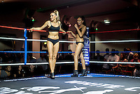 Two women in swim suits waits in the ring during an intermission at a white collar boxing event at the London Irish Centre where the 'Carpe Diem' boxing event is taking place. <br /> <br /> 'White-collar boxing' is a growing phenomenon amongst well paid office workers and professionals and has seen particular growth in financial centres like London, Hong Kong and Shanghai. It started at a blue-collar gym in Brooklyn in 1988 with a bout between an attorney and an academic and has since spread all over the world. The sport is not regulated by any professional body in the United Kingdom and is therefore potentially dangerous, as was proven by the death of a 32-year-old white-collar boxer at an event in Nottingham in June 2014. The London Irish Centre, amongst other venues, hosts a regular bout called 'Carpe Diem'. At most bouts participants fight to win. Once boxers have completed a few bouts they can participate in 'title fights' where they compete for a replica 'belt'.