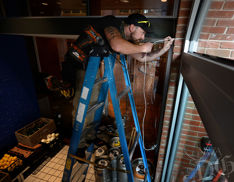 Dakota Waldo, a project manager for The Urbane Wire in Gravette, feeds data wire Thursday, July 30, 2020. to the exterior of the building while installing outdoor speakers. Waldo and a coworker were working at Tula, a Mexican restaurant on the Fayetteville downtown square. Visit nwaonline.com/200730Daily/ for today's photo gallery.<br /> (NWA Democrat-Gazette/Andy Shupe)