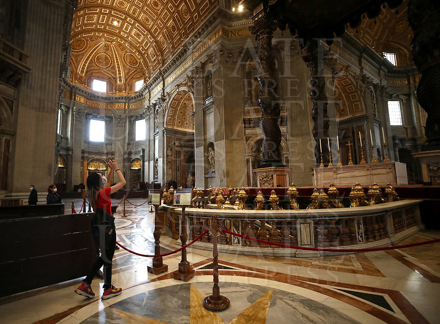 A girl takes a picture near St. Peter's Baldachin while visiting St. Peter's Basilica as it reopens on May 18, 2020 at the Vatican. Italy is slowly lifting sanitary restrictions after a two-month coronavirus lockdown.<br /> UPDATE IMAGES PRESS/Isabella Bonotto<br /> <br /> STRICTLY ONLY FOR EDITORIAL USE