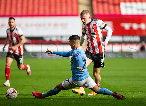 31st October 2020; Bramall Lane, Sheffield, Yorkshire, England; English Premier League Football, Sheffield United versus Manchester City; Oliver McBurnie of Sheffield United passing the ball forward as Joao Cancelo of Manchester City stretches to block the ball