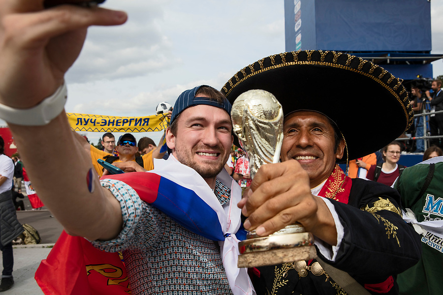 Moscow, Russia, 14/06/2018.<br /> A Russian fan takes a selfie with a Mexican supporter in the Moscow Fan Zone before the opening match between Russia and Saudi Arabia in the 2018 FIFA World Cup.