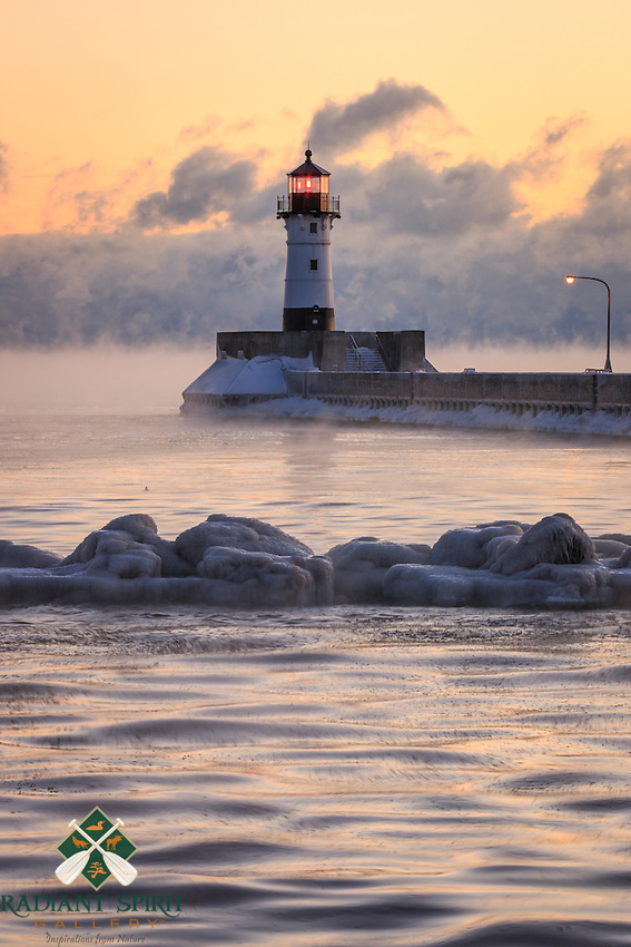 """""""Sebzero Serenity""""<br /> The hope of sea smoke inspires us to visit Lake Superior on subzero mornings. Sea smoke (winter fog) is formed when the temperature of the open water is comparatively warmer than the subzero air temperature. Relatively calm conditions allow the evaporative cooling to form plume-like fog that gracefully glides across the lake to gather in low level cloud formations. This is another one of our favorite winter weather treasures!"""